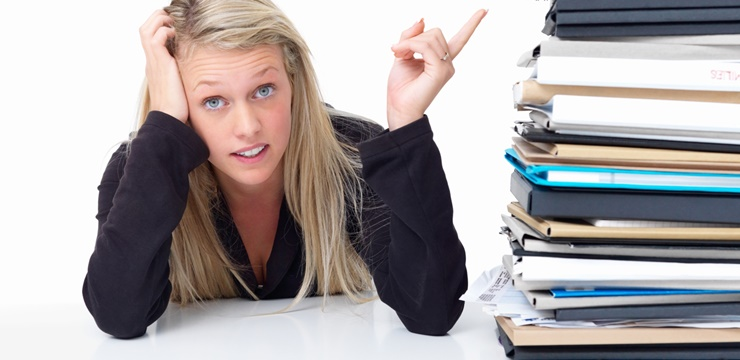 Tired business woman pointing at a stack of folders