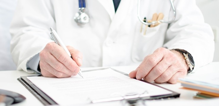 Doctor signing a medical report in his office