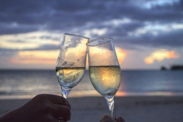 friends-toasting-with-champagne-flute-on-beach-at-sunset