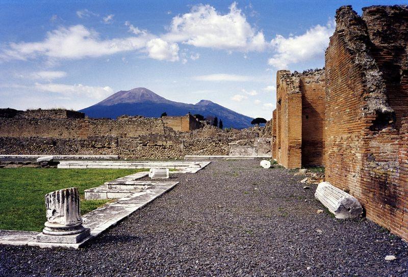 As ruínas de Pompeia, e ao fundo, o Monte Vesúvio. Fonte: Wikipedia